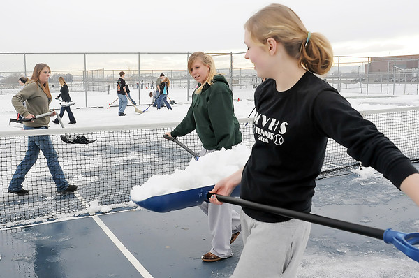Taylor Madden, 16, right, Sydney Bonar, 17, Jodi Mathis, 18, and other members of Mountain View High School's tennis team shovel snow off the courts Wednesday afternoon in preparation for the upcoming tennis season.