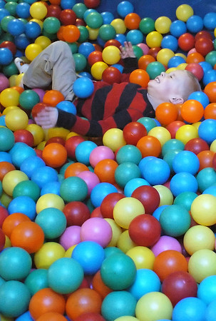 Three-year-old Jayden Bruce rolls around in the plastic balls while playing at Monkey Moe's Playhouse, 575 Denver Ave. on Thursday, Feb. 4, 2010.