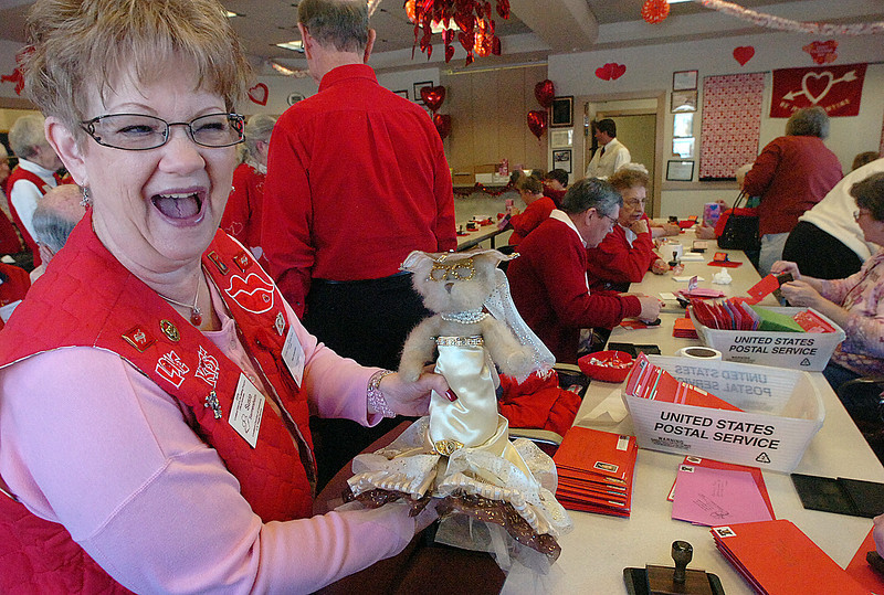 "Loveland Valentine Re- mailing Program volunteer Susie Sermersheim shows off the mascot ""Addie May"" dressed in a cappucino delight outfit Monday during the kick off of the program. Sermersheim's sister Debbie Cate, also a volunteer, made the mascot and makes different outfits for her. She also has hand crafted Valentine vest for many of the volunteers."