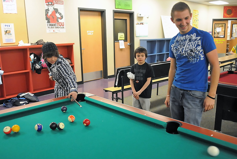 Daniel Romero, right, plays a game of pool with Anthony Hernandez, 11, left, while Ethan Hernandez, 8, looks on at the Boys and Girls Club of Larimer County's Pulliam hyouth Center, 2500 E. 1st. on Tuesday. Daniel was selected as the club's Youth of the Year.