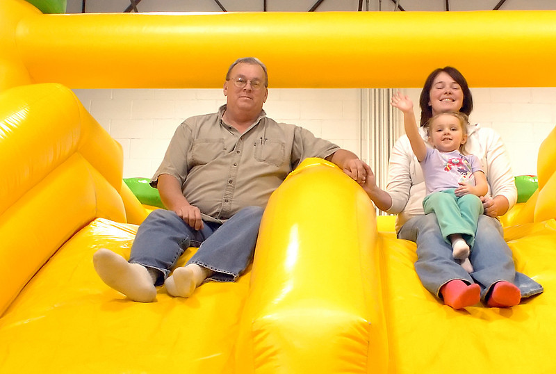 John Rodgers, Sara Rodgers and Brooke-Lynn Abalos, 2, sit atop one of the inflatables Thursday at Monkey Moe's Playhouse, 575 Denver Ave. which they opened last August. The hours of operation are Tuesday through Saturday from 10 a.m. to 7 p.m. and Sundays from noon to 6 p.m.