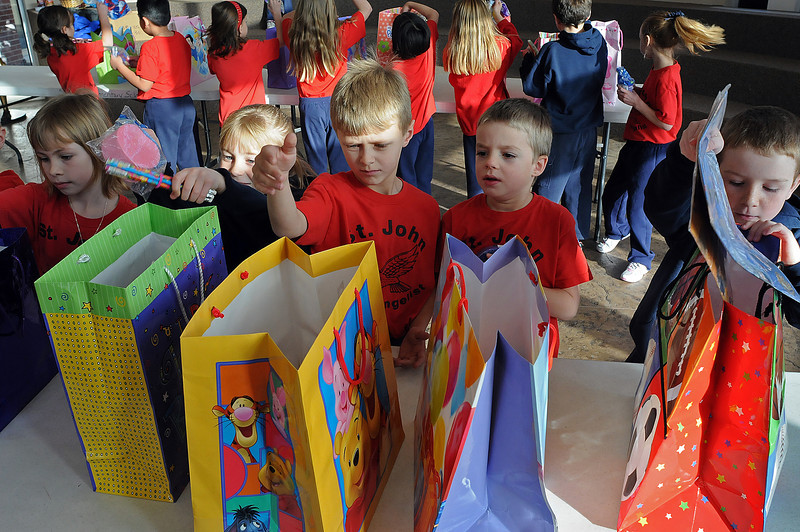 First-graders from Shannon Lotz' class at Saint John the Evangelist School, from left, Roni Hennessey, 7, Mackenzie Love, 6, Keaton Stroh, 7, Gage Delich, 6, and Hunter Stansbury, 6, fill bags with decorations and party supplies on Monday at the school. The gift bags, filled with cake, frosting, decorations and just about everything needed for a child's birthday party, will be delivered to the House of Neighborly Service and given to parents who aren't able to provide the necessary items for their child's party.