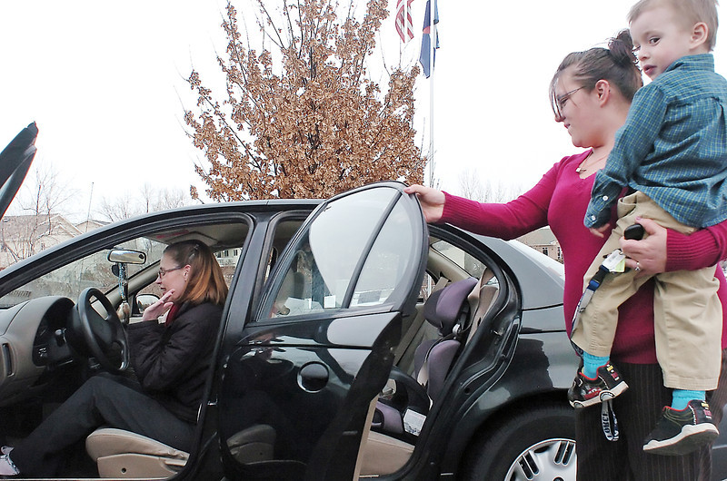 Loveland resident Nicolle Gregg sits for one last time Wednesday behind the wheel of the car she donated recently to Project Self-Sufficiency and was given to Marlana Rivers who looks on with her 2-year-old son, Ryan Witman. When Gregg donated the car she didn't have a chance to say goodbye to it and was happy to meet the car's new owner and also say farewell to her faithful companion for 10 years.