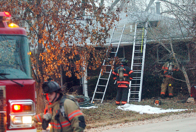 Loveland Fire and Rescue Department personnel work the scene of a house fire Wednesday at 1909 W. 24th St. in west Loveland.