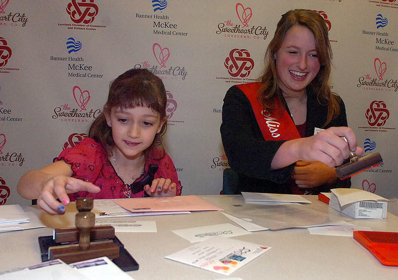 Ms. Loveland Valentine, Hillary Skeffington, right, and 7-year-old Samantha Connolly stamp some of the first Valentines during the kick off of the Re-Mailing Program.