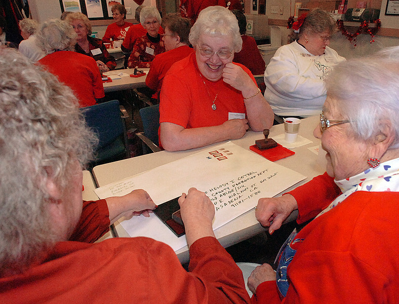 Loveland Valentine Re- mailing Program volunteer Fay Olbert, left, stamps a huge Valentine as Bess Lewis, right, and Maxine Johnson, center, share a laugh.