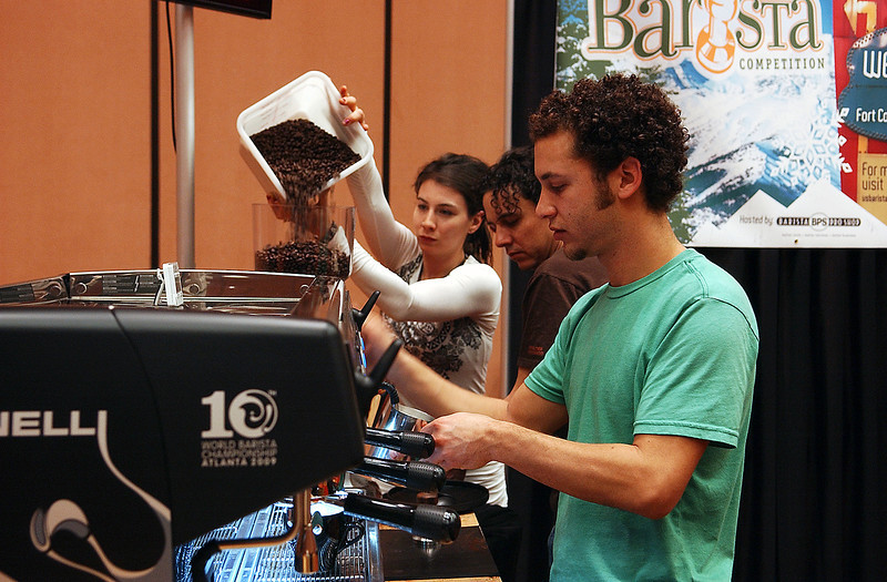 "Greg Lefcourt, practices to defend his title of Rocky Mountain Barista winnner with coworkers from Ozo Coffee Company in Boulder, Zoe Clare and Justin Hartman Saturday, Feb 13.  As Director of Retail Operations, Lefcourt comments to his friend and earlier competition, ""I'm not just a barista anymore, Zoe."""