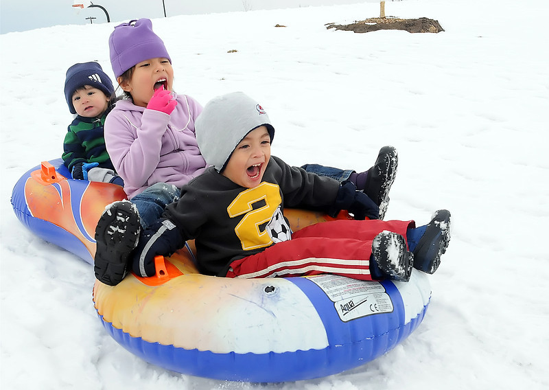 Two-year-old Noah Duran, front, his sister, Felicia, 5, and brother, Jovani, 1, slide down a hill on a snow tube while spending Wednesday afternoon playing together with their parents at the Loveland Sports Park.