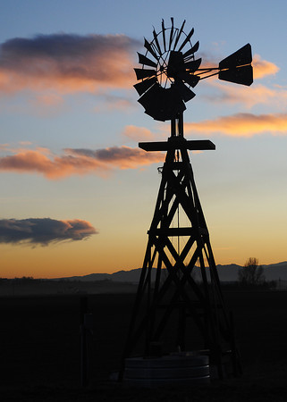 A windmill is silhouetted by wisps of clouds reflecting multi-colors from the setting sun Tuesday evening southeast of Berthoud.