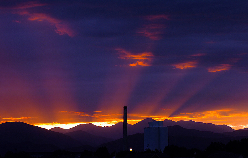 Orange rays from the setting sun stream between mountain peaks and over the old sugar factory on Friday, Sept. 12, 2009, in this view from east Loveland.