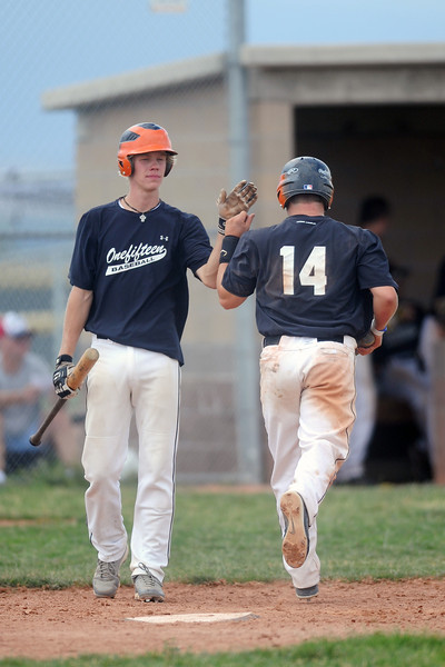 Chris Sievers, left, congratulates teammate Mike Medina after he scored a run during game two of a doubleheader against Slammers Grey at Erie High School on Saturday, July 7, 2012.