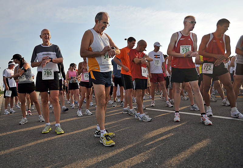 Runners make final glances at their watches before taking off for the 5K and the 10K races Saturday during the Loveland Classic at Centerra.