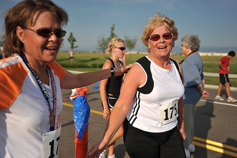 "Cindie Mearsha, right, smiles as her friend Marlene Graff greets her after finishing the 5K Loveland Classic at Centerra on Saturday. The run marked Mearsha's hundreth race since 2002, and she met her goal of participating in 100 races before the age of 60, ""I turned 58 in June!"" she proclaimed with a smile."