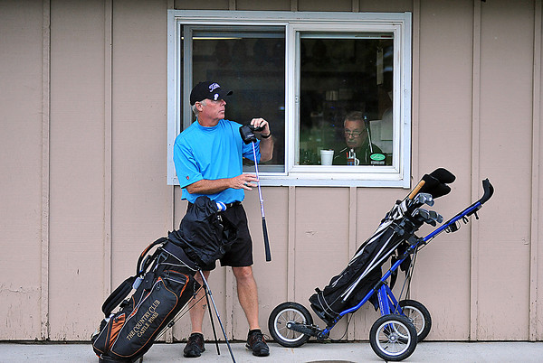 """Charles Malone of Castlerock pulls out a club Wednesday as he prepares take a few putts next to the pro shop at the Old Course in Loveland. In the window staffer Warren Boizot looks on from a quiet shop. Though the Old Course seems to be attracting a good number of golfers, the pro shop has seen a drop in sales, """"we definitely feel the crunch,"""" says the Head Golf Pro Kim Stiner (not pictured)."""