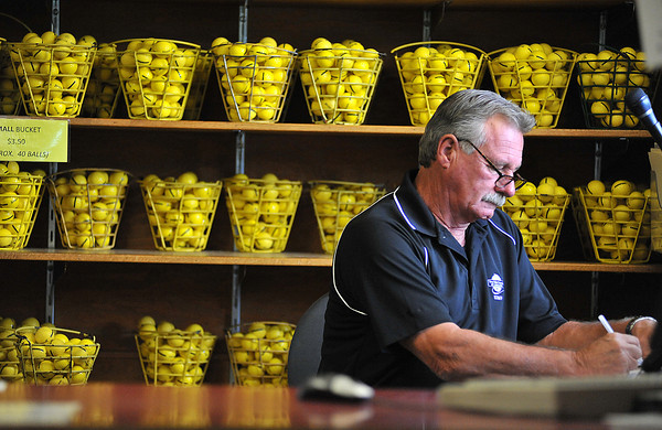"""Warren Boizot, a part time pro shop worker at The Olde Course golf green in Loveland looks out the window Wednesday as he waits for customers. While course play doesn't seem to be dropping much, pro shop sales have taken a hit, """"we definitely feel the crunch"""" says Kim Stiner, the Head Golf Pro at the course."""