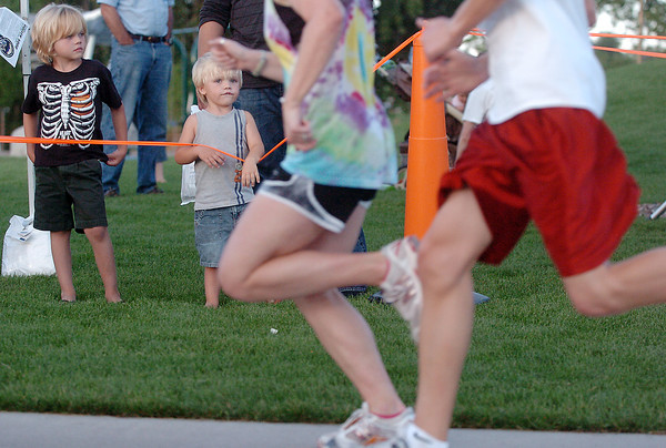 Five-year-old Jake Schmidt, left, and his brother, Brock, 2, watch runners sprint past toward the finish line of the Valley 5000 as the wait to cheer on their mother and grandmother who were competing in the run Friday evening at Fairgrounds Park.