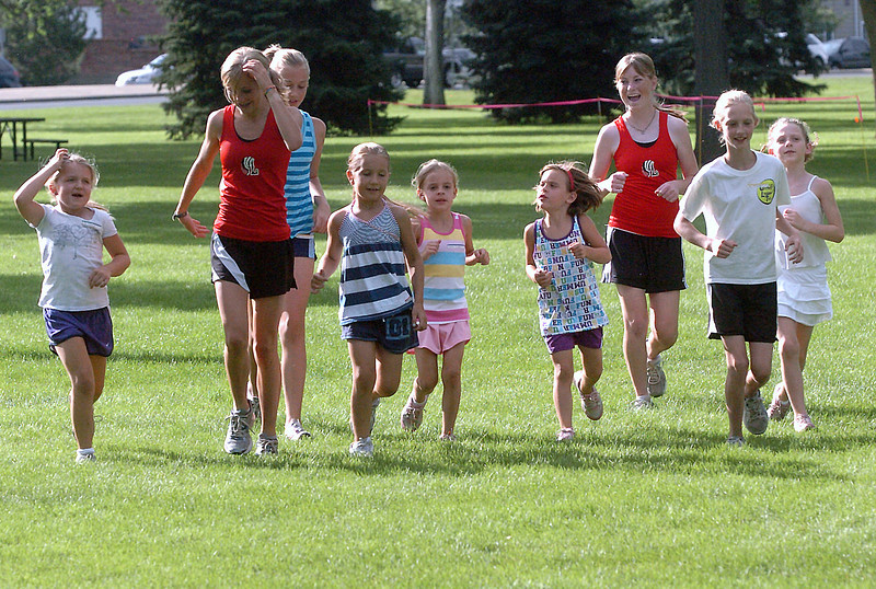 Runners warm up together before the start of a fun run Friday at North Lake Park. From left to right are Ali O'Donnell, 7, Kailie Hartman, Rebekah Circenis, 11, Chloe Circenis, 7, Kenadi Krueger, 8, Olivia Krueger, 6, Amanda Cunningham, Ava McQuade, 10, and Livia McQuade, 6. Members of Loveland High School's cross country team started a program to get girls in elementary school interested in running for fun and also the sport of cross country.