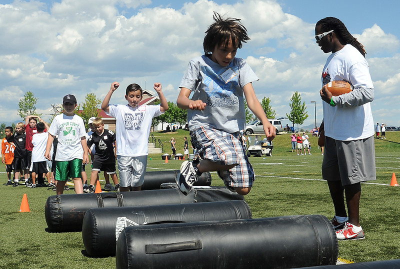 Volunteer coach Thomas Smith, right, looks on as Mason Rykovich, 9, front, and others leap over a pads during a drill Saturday as part of Jeremy Bloom's Youth Football Camp at the Loveland Sports Park.