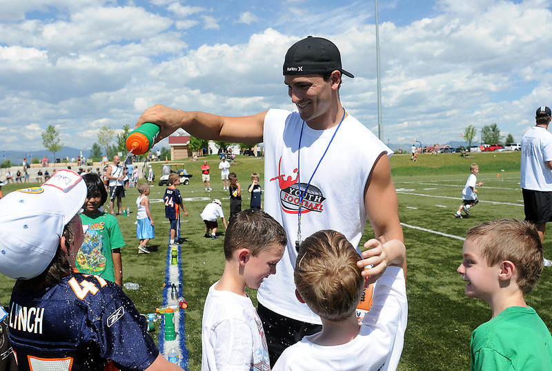 Jeremy Bloom squirts water on kids to cool them off during during his youth football camp Saturday at the Loveland Sports Park.