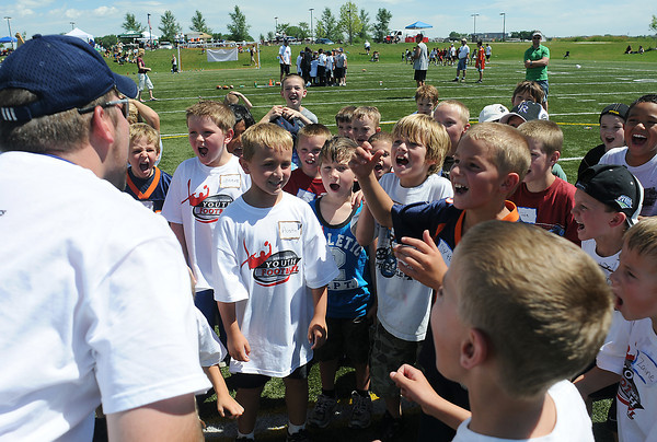 Volunteer coach Cabel Rohloff, left, fires up youngsters before a drill Saturday during Jeremy Bloom's Youth Football Camp at the Loveland Sports Park.
