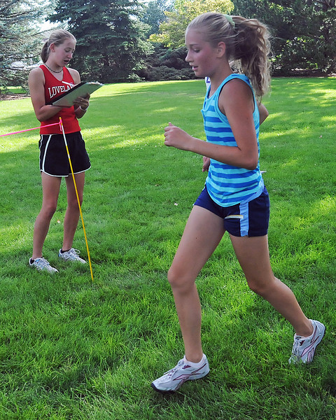 Loveland High School junior and cross country team member Torrey Stephenson, left, writes down the time for Rebekah Circenis, 11, as she crosses the finish line during a fun run Friday at North Lake Park.