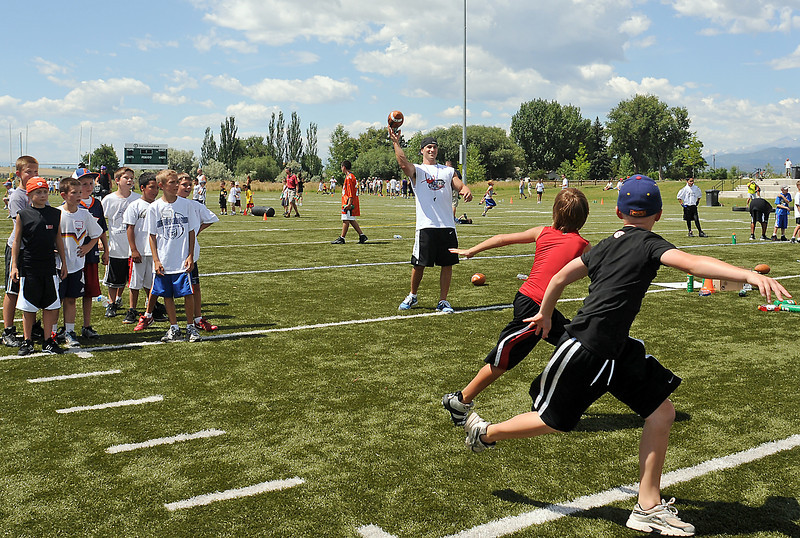 Jeremy Bloom, center, throws a pass during a drill Saturday at his youth football camp at the Loveland Sports Park.