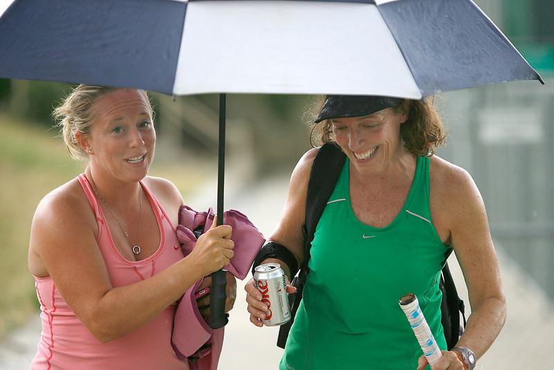 Dawn Petersen holds an umbrella for.... during the Loveland Open Sunday at Loveland High School.