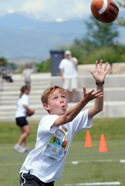 Erie resident Hunter Goodman, 10, goes up for a catch Saturday while participating in the Jeremy Bloom's Youth Football Camp at the Loveland Sports Park.