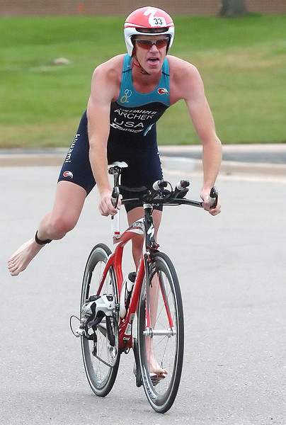 Jimmy Archer prepares to dismount after completing the cycling portion of the Loveland Sprint Triathlon on Saturday at North Lake Park before completing the final 5-kilometer run to become the best male finisher of the race.