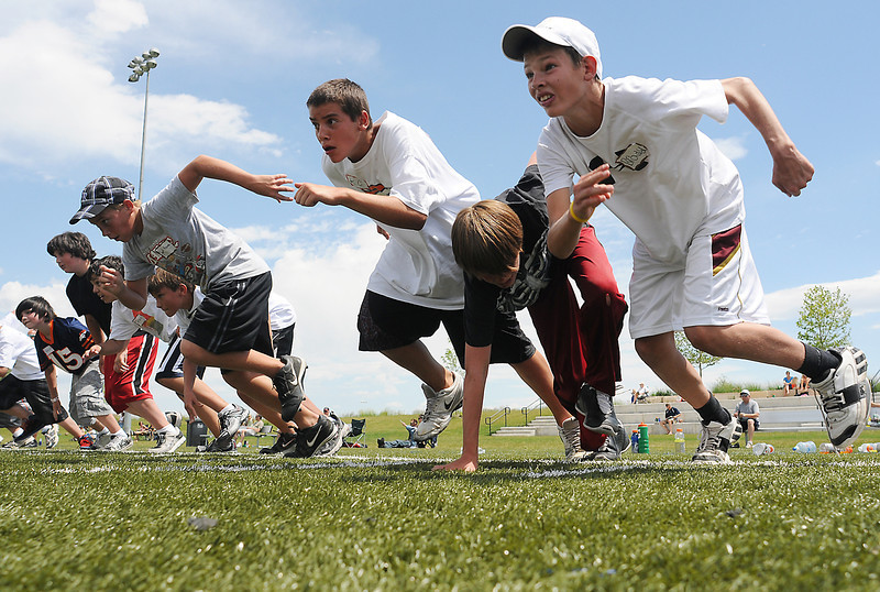 Windsor resident Brady Bowman, 12, right, blasts off the line with other youngsters during Jeremy Bloom's Youth Football Camp on Saturday at the Loveland Sports Park.