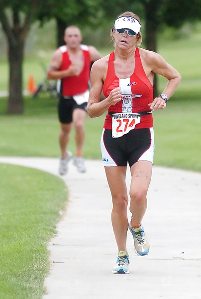 Jane Esahak-Gage of Arizona runs down the final stretch to become the best female finisher during the Loveland Sprint Triathlon on Saturday at North Lake Park.