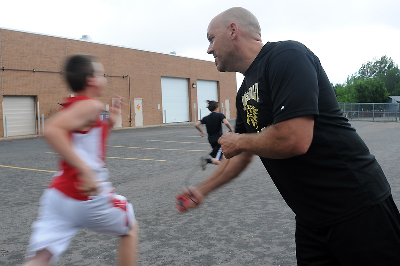 Thompson Valley High School freshmen Justin Riley, 14, left, and Logan Jaramillo, 14, speed by as head football coach Michael DeWall uses a stopwatch to time them in a 40-yard dash drill before their weight training session Thursday at the school. Photo by Steve Stoner