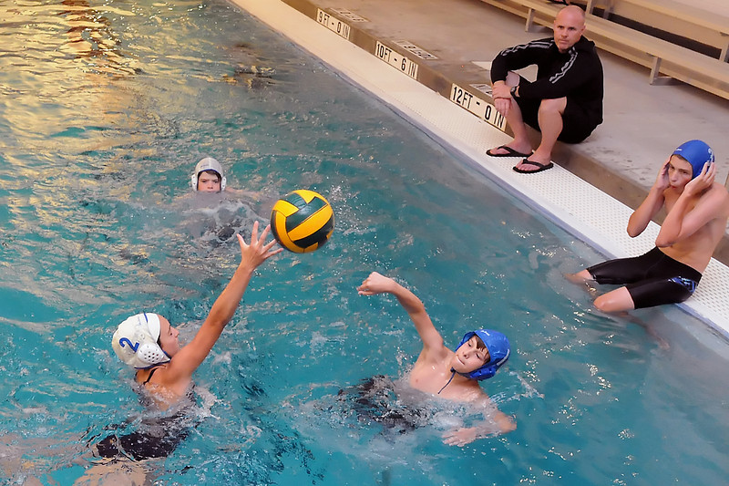 Megan Abeyta, 16, left, attempts to block a shot by Dillon Einarsen-Bradley 13, during a water polo practice Wednesday, June 29, 2011 at Loveland High School's pool. Back from left are Bryan Smith, 13, coach Keith Leggett and Nate Denesha, 15.