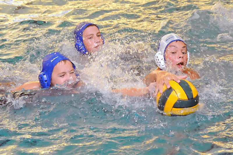 James Denesha, 13, left, Nate Denesha, 15, and Jeremy Abeyta, 14, track down the ball while working on a drill during water polo practice Wednesday, June 29, 2011  at the Loveland High School pool.