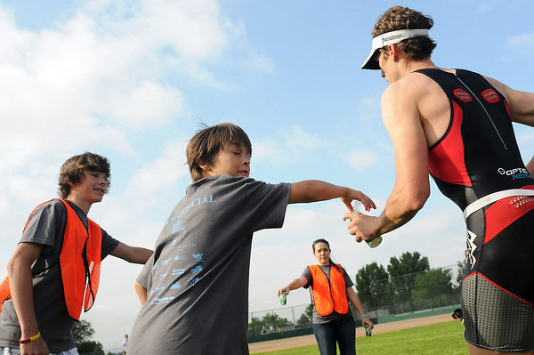 Lake To Lake Triathlon volunteers Alex Marr, 13, left, Spencer Bean, 12, and Nena Casey, 16, back, hand out water to participants at the start of the running stage on Saturday morning at North Lake Park.
