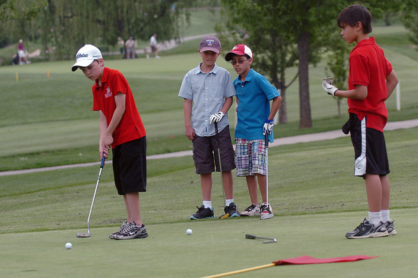 Jayden McLaughlin, 10, left, hits a putt on No. 9 while Henry Stucky, 11, Micah Ramirez, 11, and Daniel Smith, 11, look on while the boys compete in the Loveland Optimist Junior Tournament on Monday, June 6, 2011 at The Olde Course.