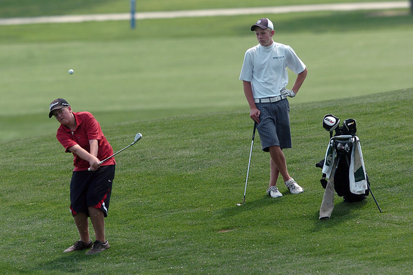 Cole Bundy, 15, right, looks on while Riley Sarbacker hits a shot while the two participate in the Loveland Optimist Junior Tournament on Monday, June 6, 2011 at The Olde Course at Loveland.