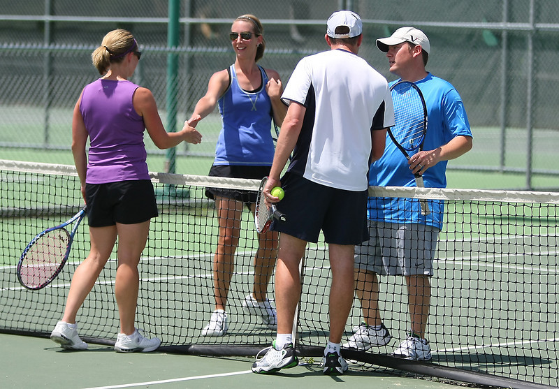 Kelly Blanks, in purple, shakes hands with her siste,r Erin Hauser-Roe, while Brian Smith, in white, shakes hands with Nick Roe after the 4.0 mixed doubles finals during the Debbie Boose Memorial Tennis Tournament Sunday at North Lake Park Courts. Blanks and Smith won the match 4-6 6-4 1-0 (6) against the married couple. The tournament raised money for Pathways Hospice.