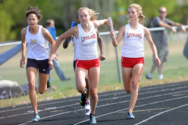 Loveland High School's Kailey Fuchs, right, hands the baton to teammate Taylor Buschy while competing in the 400-meter relay during the R2-J Invitational on Friday, April 20, 2012 at LHS.