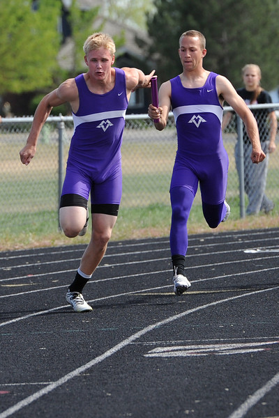 Mountain View High School's Connor Logan, right, hands the baton to teammate Josh Sandin while competing in the 400-meter relay during the R2-J Invitational on Friday, April 20, 2012 at Loveland High School.