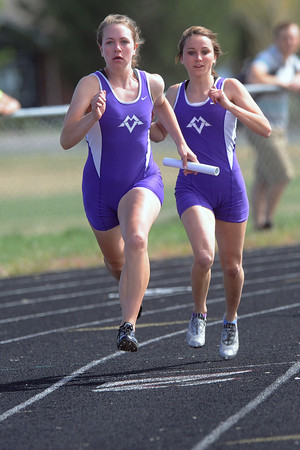 Mountain View High School's Allison Lenart, left, sprints away from teammate Kacey Uhlenbrock after receiving the baton in the 400-meter relay during the R2-J Invitational on Friday, April 20, 2012 at Loveland High School.