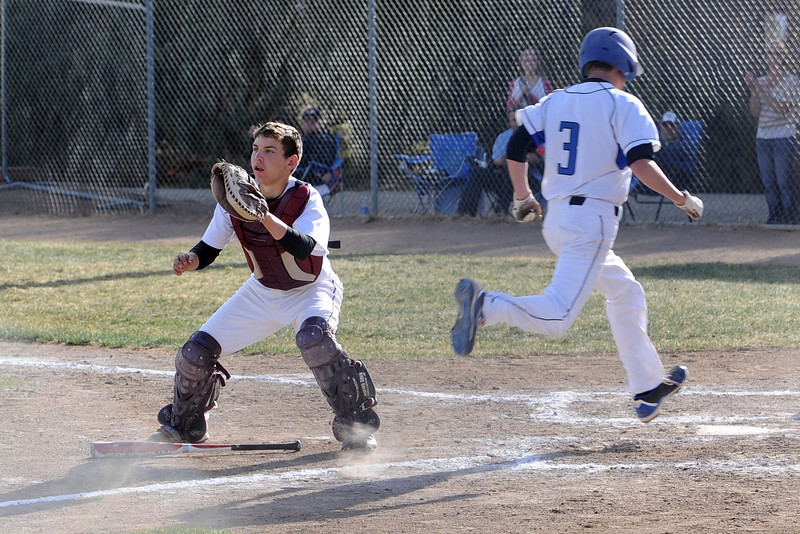 Berthoud High School catcher Nate Ruebesam waits for the ball while Resurrection Christian's Brett Bakersky scores a run in the top of the fifth inning of their game on Thursday, April 5, 2012 at Sommers Field.