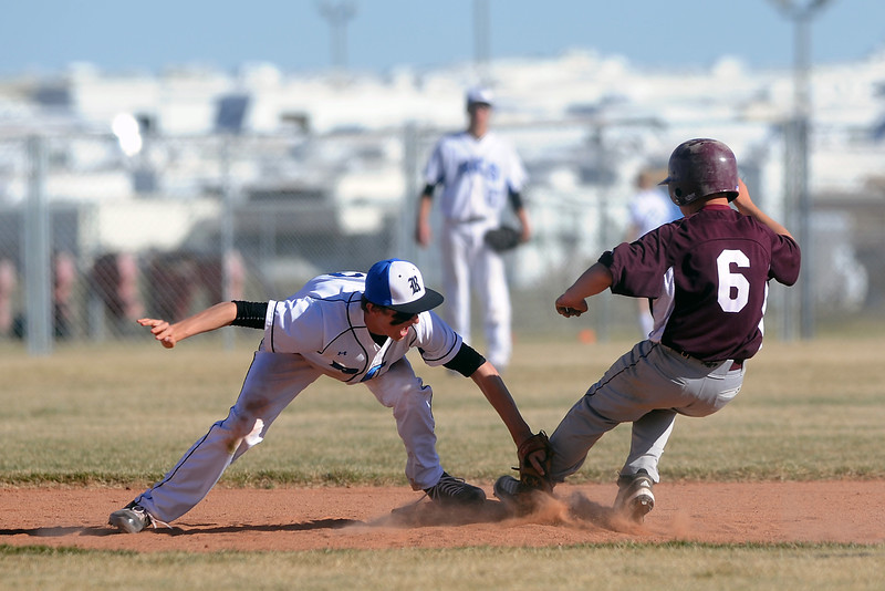 Berthoud High School baserunner Austin Bending steps on second base just ahead of the tag by Resurrection Christian School shortstop Brett Bakersky after a failed pickoff attempt at first base in the top of the third inning of their game Friday, March 23, 2012 at RCS. The Cougars won in five innings, 12-2.