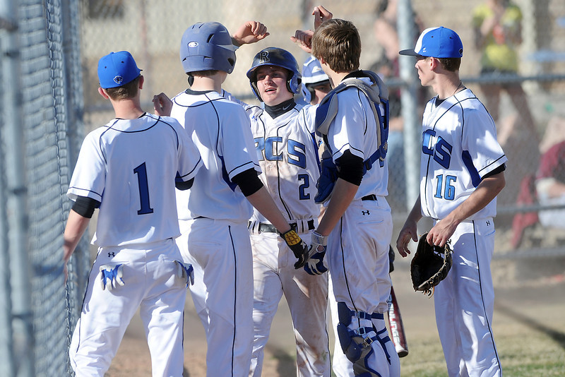 Resurrection Christian School's Josh Mondt (2) is congratulated by teammates at the dugout after scoring a run from third base on a wild pitch in the bottom of the third inning of a game against Berthoud on Friday, March 23, 2012 at RCS. The Cougars won in five innings, 12-2.