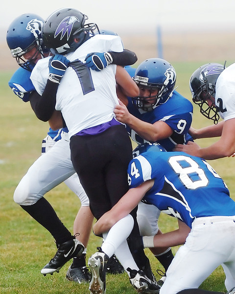 Front Range Christian School quarterback Matthew Chacon is tackled by Resurrection Christian defenders Jon Sysum, left, Caleb Boehler (9) and Paul White (84) in the first quarter of their game Saturday afternoon at RCS.