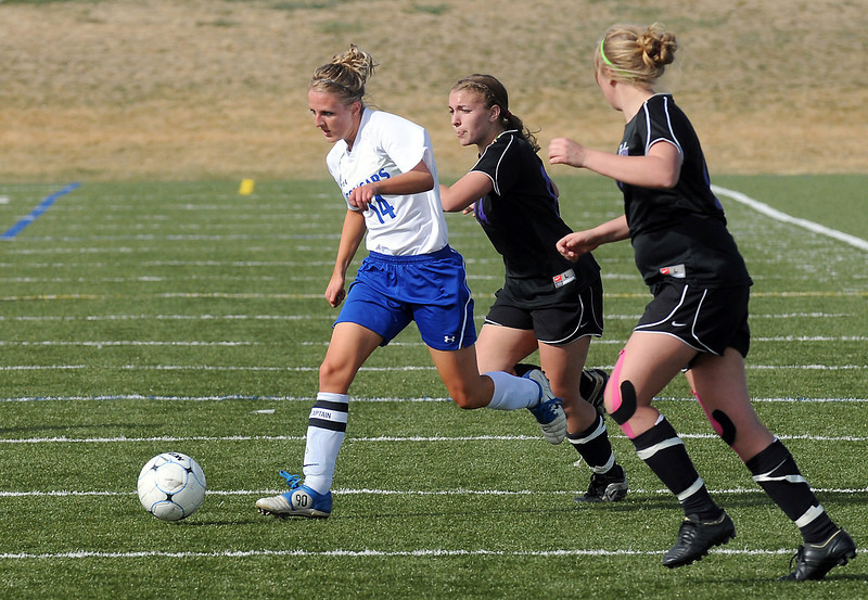 Resurrection Christian School senior Courtney Brand, left, dribbles away from Lutheran-Parker's Sarah Mayhall and Alex Winters in the second half of their game Friday at the Loveland Sports Park. The Cougars won, 3-1.