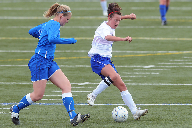 Resurrection Christian School senior Alyssa Parrott, right, and Alexander Dawson's Emily Oliver track down the ball in the first half of their match Friday at the Loveland Sports Park. The Cougars lost, 1-0.