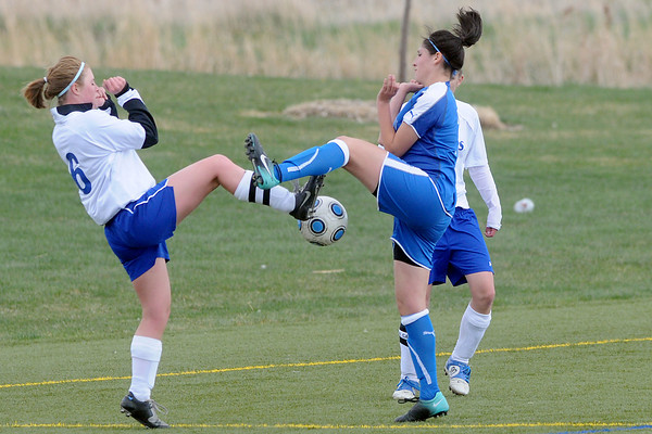 Resurrection Christian School senior Audrey Isabelle, left, goes up against Alexander Dawson's Crystal Chavez while Courtney Brand looks on in the first half of their match Friday at the Loveland Sports Park. The Cougars lost, 1-0.