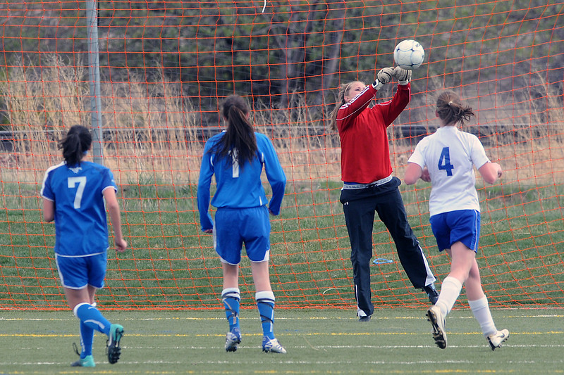Resurrection Christian School's goalie punches the ball away in the first half of a match against Alexander Dawson School on Friday at the Loveland Sports Park.