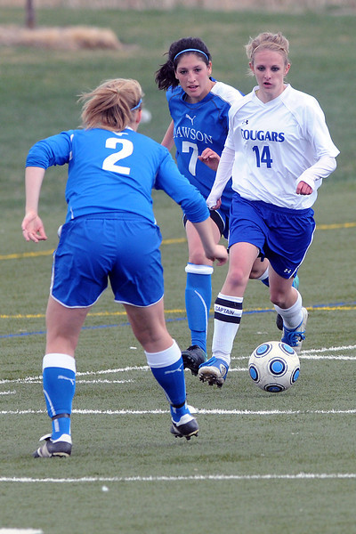 Resurrection Christian School senior Courtney Brand (14) dribbles around Alexander Dawson's Emily Oliver (2) and Crystal Chavez (7) in the first half of their match Friday at the Loveland Sports Park. The Cougars lost, 1-0.